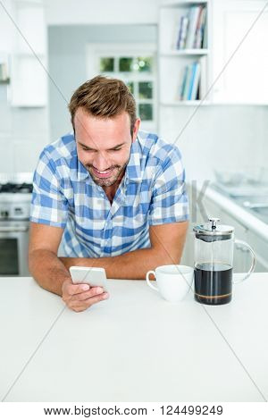 Happy man using mobile phone while leaning on table in kitchen at home