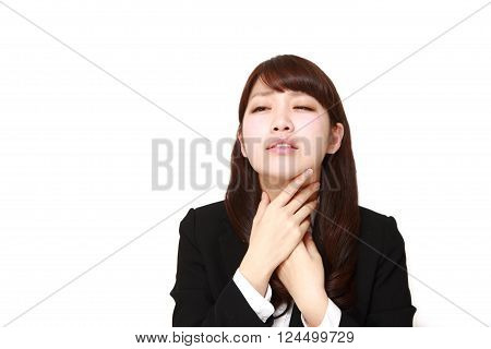 portrait of young Japanese businesswoman having throat pain