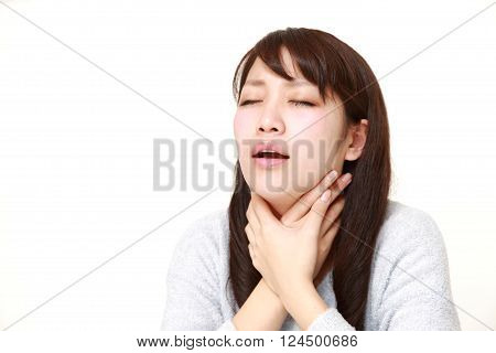 portrait of young Japanese woman having throat pain