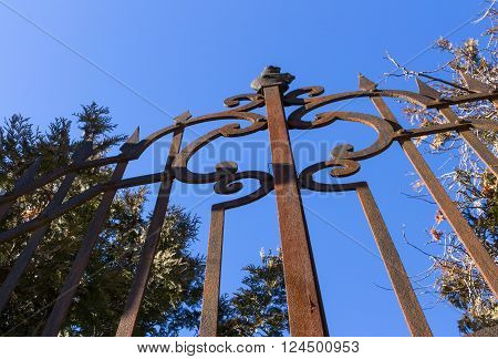 Close-up of wrought-iron rusted fence against blue sky