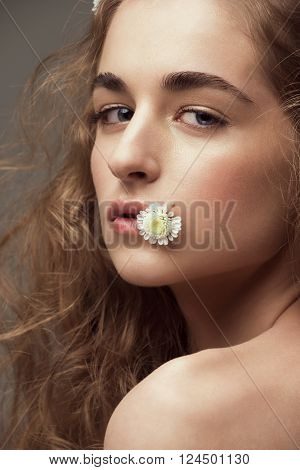 Young beautiful woman with perfect healthy skin with flower in her mouth