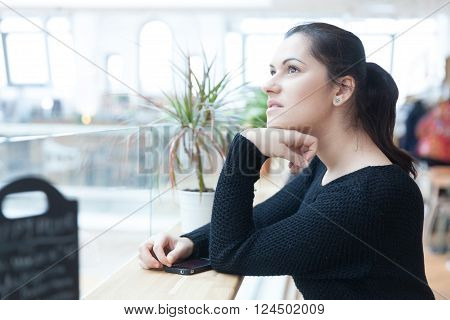 Lovely young woman having a daydreaming moment.