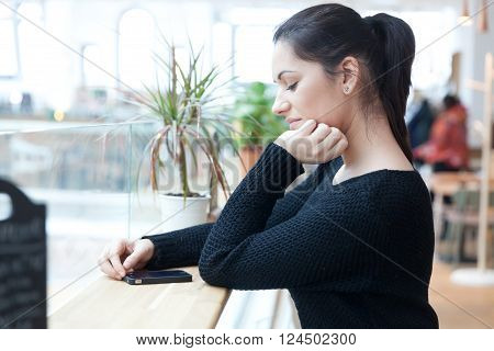 Young woman ignoring the environment being addicted to social media. Conceptual image with people pretending that are always using phones or tablets in normal life.