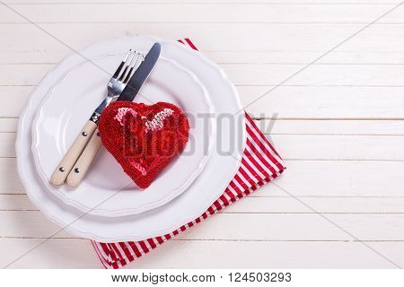 Romantic table setting. Red and white. Decorative red heart knife and fork on white plate on white wooden background. Selective focus. Place for text.
