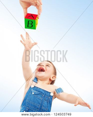 Happy child having fun, cute cheerful little boy stretches to take cube with the letters from mother's hand over clean blue-white background, enjoying education