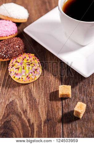 Coffee and marshmallow biscuits with icing colored granules on wood table
