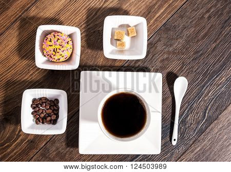 Cup of coffee with brown sugar coffee beans and marshmallow biscuit in white ceramic