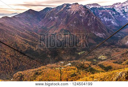 Ropeway Cable transport wires and cables leading to the valley. Gondola track with the forest and woods in autumn colors. Landscape picture of Slovenia travel destination for vacation.