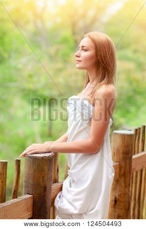 Gentle woman wrapped in bedsheet standing on terrace, enjoying fresh summer nature and fresh air, relaxation on spa resort