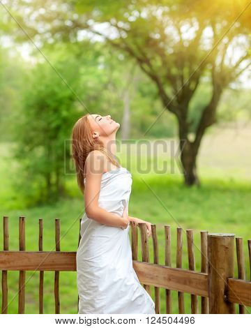 Beautiful calm female with pleasure spending time on spa resort, covered in white bedsheet standing on the balcony and with closed eyes enjoying sun rays