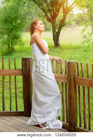 Gentle woman wrapped in the bedsheet standing on terrace and enjoying fresh summer nature, relaxation on spa resort