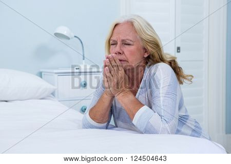 Senior woman praying in bedroom at home