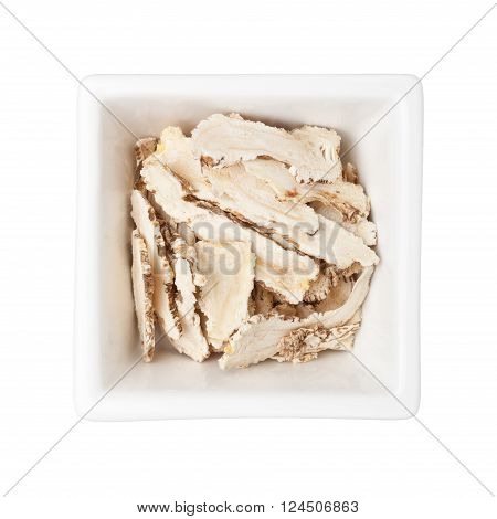 Traditional Chinese Medicine - Sliced danggui in a square bowl isolated on white background