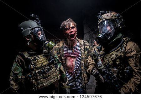 KIEV,UKRAINE - February 20 : Crazy zombie with terrible bloody face attacks two soldiers with guns during a thematic game about zombies in Kiev,Ukraine on February 20,2016.