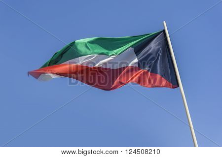 Kuwait flag flying on a bright blue sky day