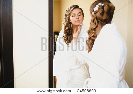 The girl in white coat at the mirror preening