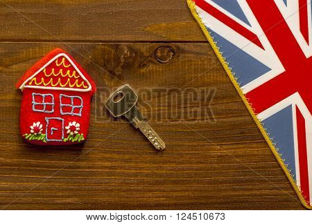 Red sweet house key and british flag on wooden background