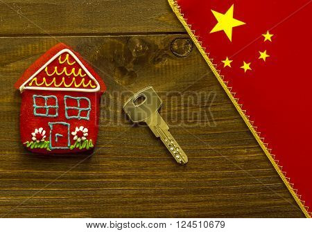 Red sweet house key and chinese flag on wooden background
