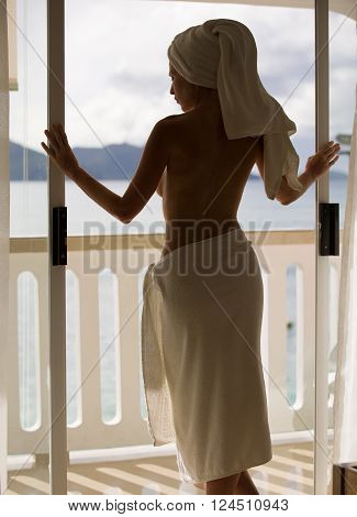 Beautiful and sexy nude woman on balcony, in hotel room