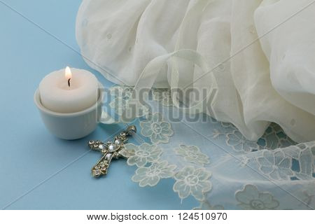 Close up shot of vintage babtism dress on blue background with cross and candle