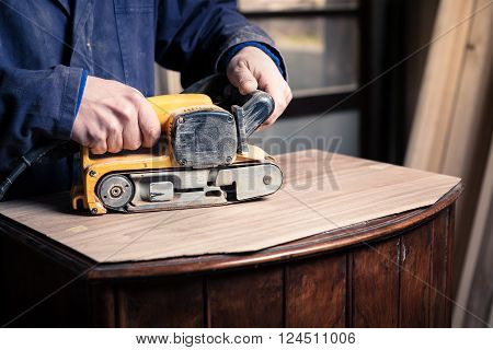 Carpenter Restoring Furniture With Belt Sander