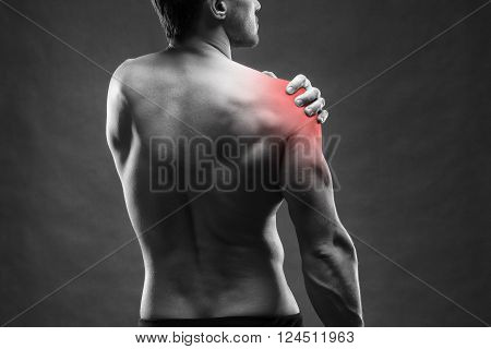 Pain in the shoulder. Muscular male body. Handsome bodybuilder posing on gray background. Black and white photo with red dot