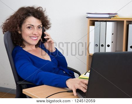 Relaxed And Smiling Businesswoman Sitting With Laptop At Desk In Office