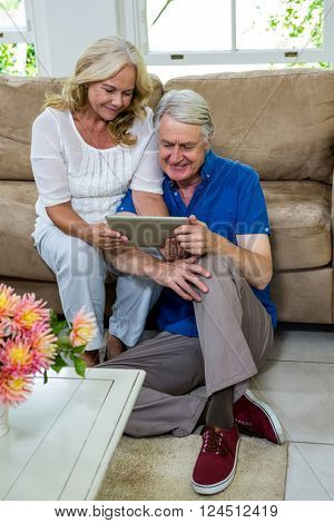 High angle view of senior couple using digital tablet in living room at home