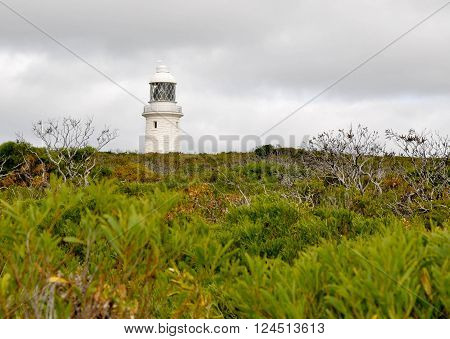 Old Cape Naturaliste Lighthouse in the coastal green vegetated dunes on the Leeuwin-Naturaliste ridge in Dunsborough, Western Australia under stormy skies.