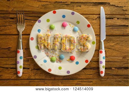 The word KIDS written in cake on a spotty plate and matching cutlery
