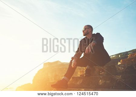 Young handsome man fashion model dressed in stylish clothes is enjoying warm day and leisure while is sitting on stone rock against blue sky and sunshine with copy space background for your content