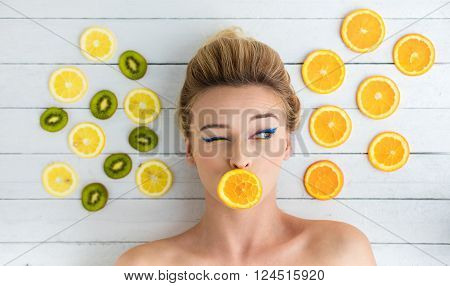 Blonde Woman Laying Next To Slices Of Orange, Lemon And Kiwi