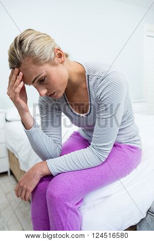 Young woman with headache sitting on bed at home