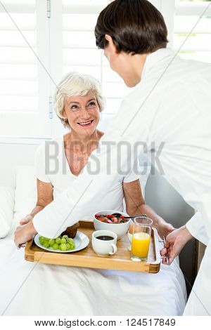 Female caregiver serving breakfast to old woman at home