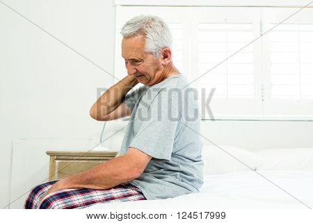 Senior man suffering from neck ache on bed at home