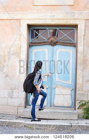 Attractive young female tourist opening door to a hostel.