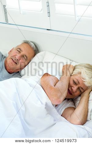 High angle view of irritated senior woman sleeping by snoring man on bed at home