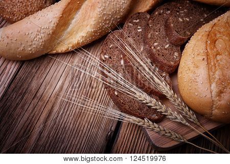 Fresh bread, sweet pastries, baked goods, harvest on the farm, delicious food, ears of wheat, healthy food, a table of old wood, bread closeup