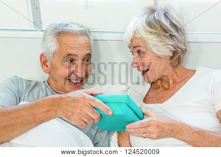 Senior man and woman holding gift box on bed at home