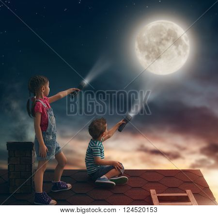 Two cute children sit on the roof and look at the moon.