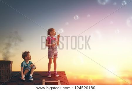 happy childhood! boy and girl playing on the roof. child blowing soap bubbles.