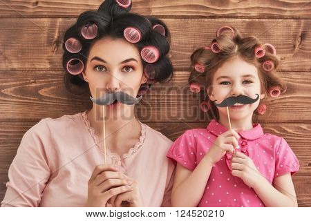 Funny family! Mother and her child daughter girl with a paper accessories. Beauty funny girl holding paper mustache on stick. Beautiful young woman holding paper mustache on stick.