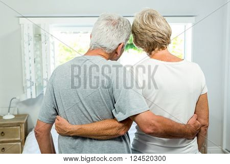 Rear view of senior couple with arm around standing against window at home