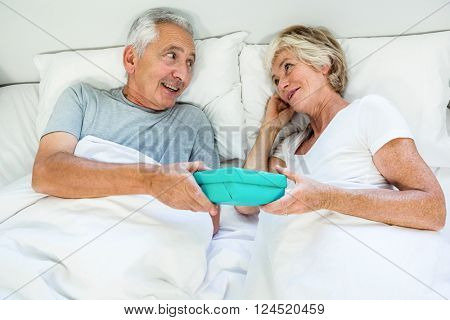 High angle view of senior man and woman holding gift box on bed at home