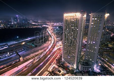 Highway junction and high residential buildings at night in Moscow, long exposure