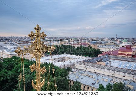 Gilded cross of Spas-na-krovi cathedral and view of evening St. Petersburg, Russia