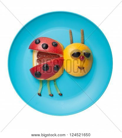 Ladybird made of fruits on blue plate