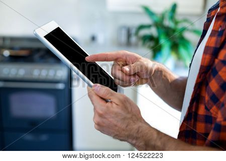 Mid-section of man using digital tablet at home