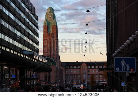 Helsinki, Finland - 29 Oct  2015: Evening view of the city: the main railroad station with the clock tower and street with  shopping complex on the sunset, on Oct 29 2015, Helsinki, Finland