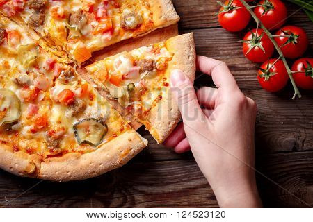 Hand picking tasty slice of pizza lying on wooden table, Focused on hand.